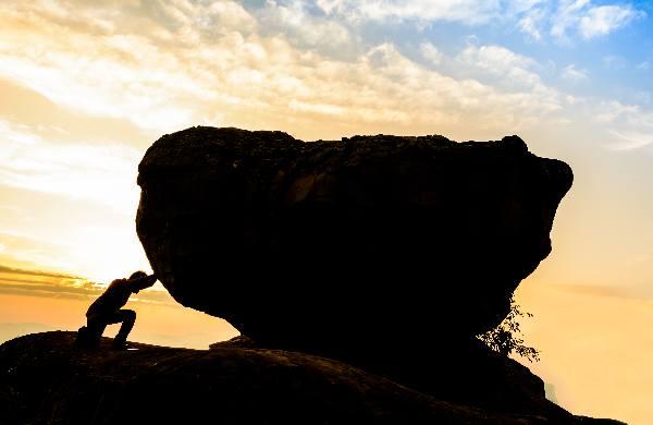 homme poussant une pierre risques liés à l'activité physique